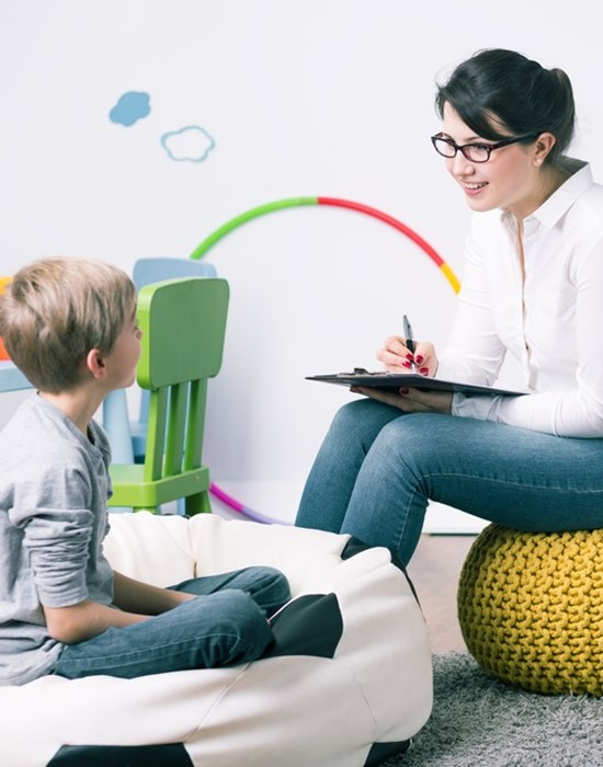 Woman sitting in front of a child with a clip board