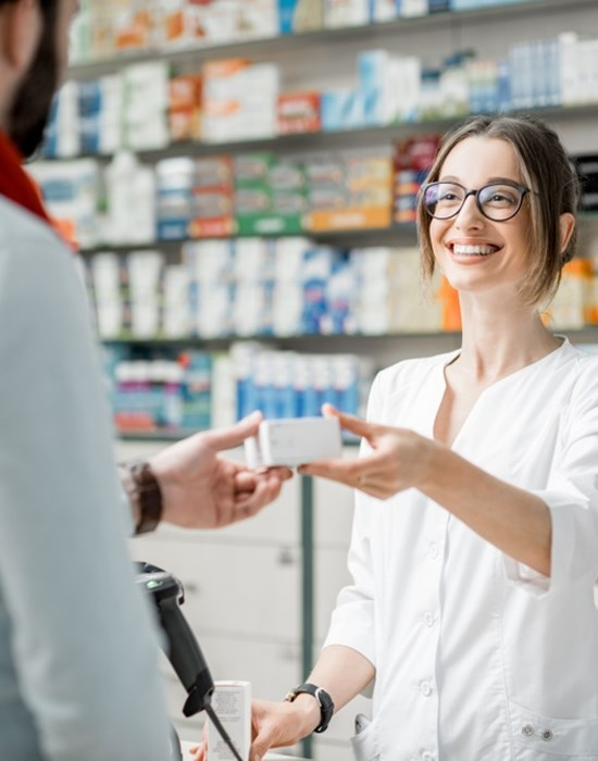 Pharmacist giving man his prescription